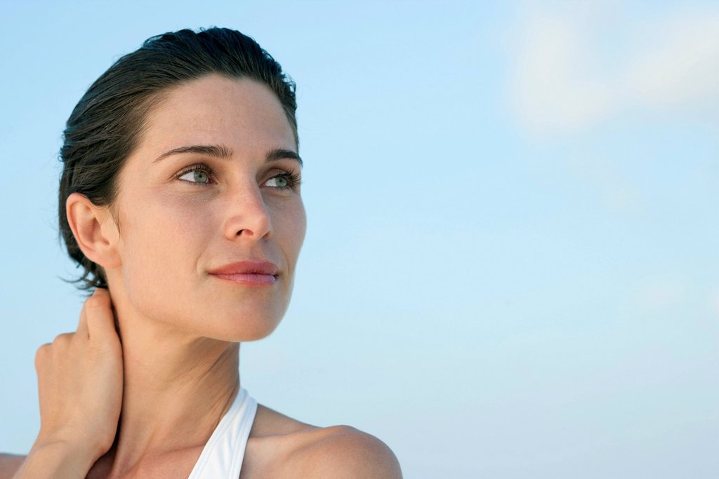 Woman touching neck, looking up in thought : Stock Photo