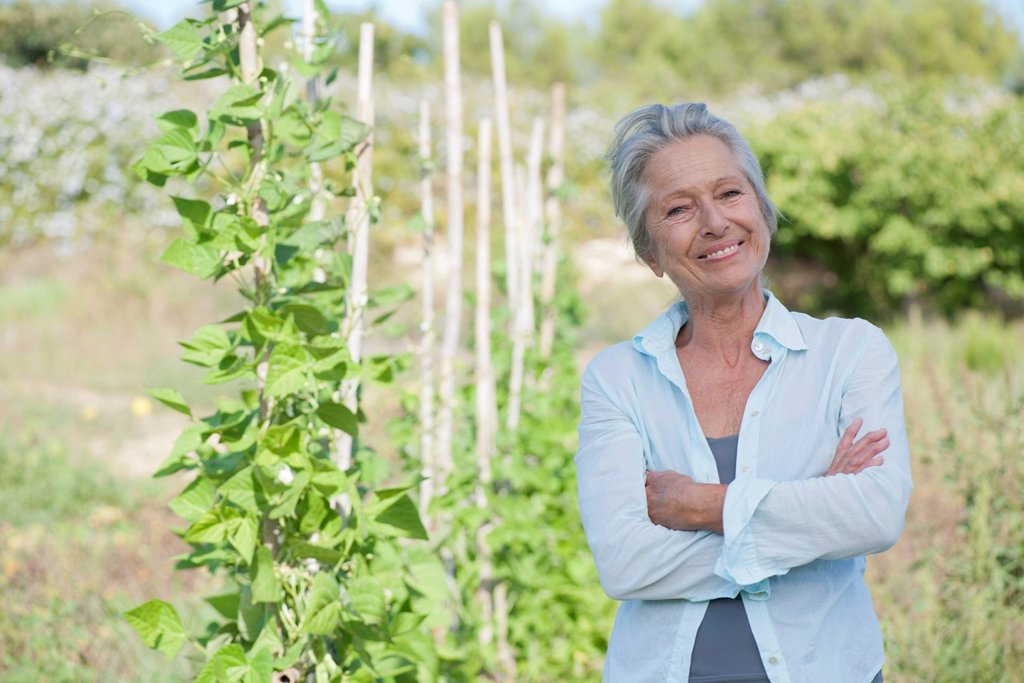 Stock Photo: 1747R-18742 Senior woman smiling proudly in vegetable garden