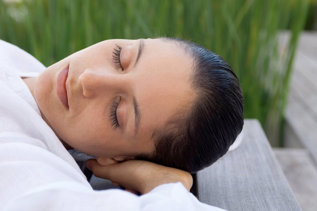 Woman lying down with hands behind head outdoors : Stock Photo