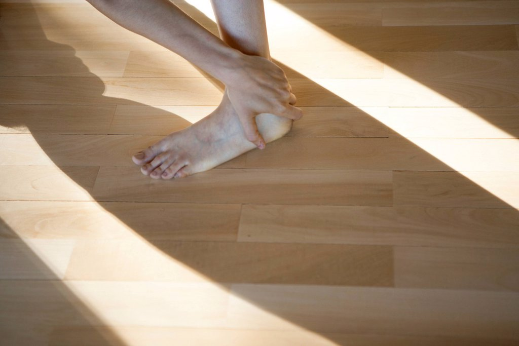 Stock Photo: 1747R-18783 Woman touching ankle, low section, cropped