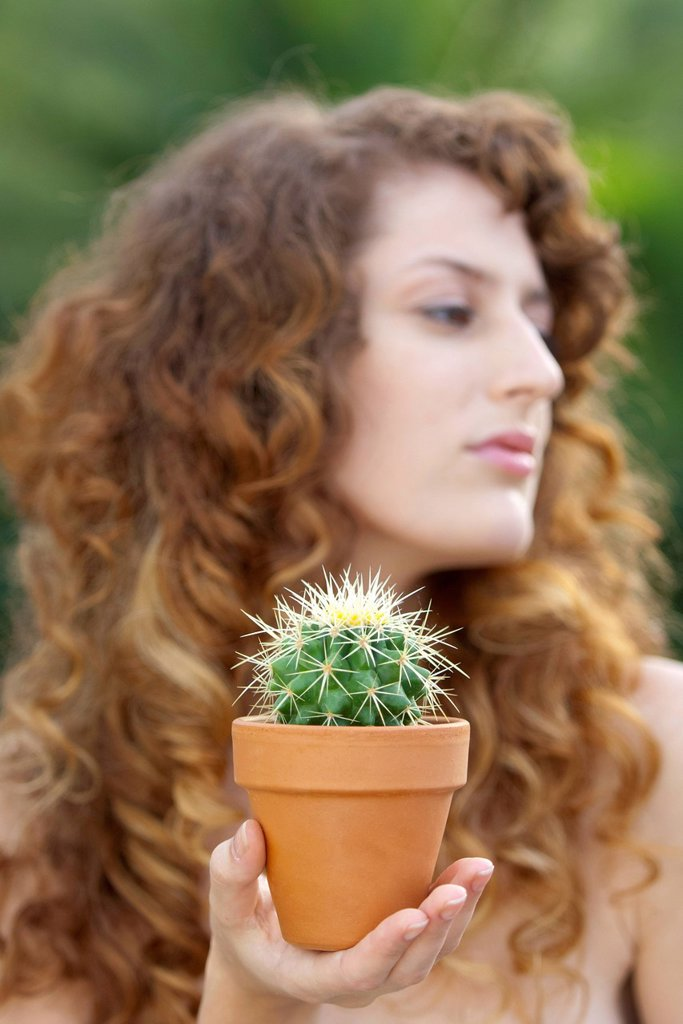 Stock Photo: 1747R-18800 Woman holding potted cactus in palm, looking away