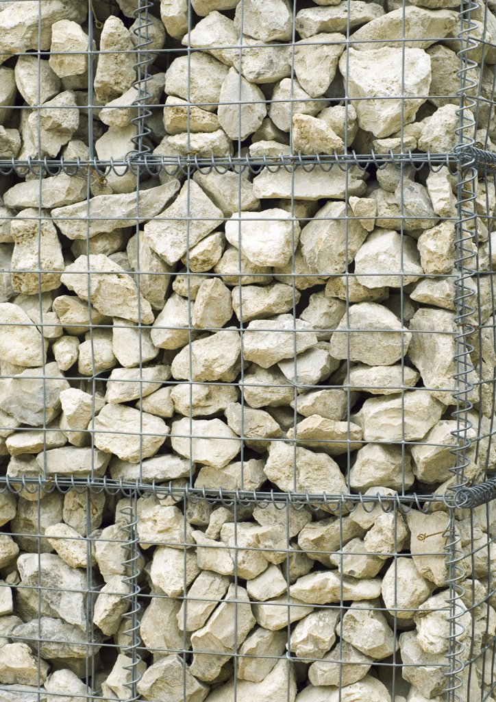 Stock Photo: 1747R-2721 Stone wall contained by wire mesh, close-up