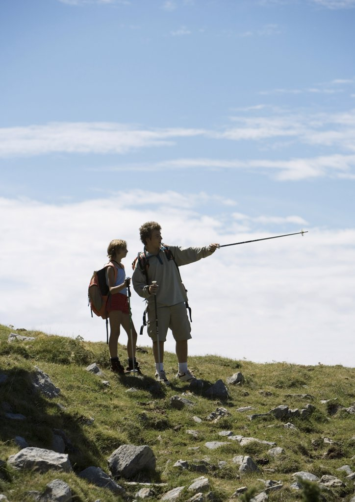 Hikers, man pointing with walking stick : Stock Photo