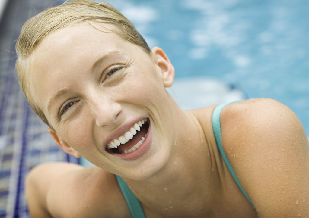 Young woman laughing, pool in background : Stock Photo