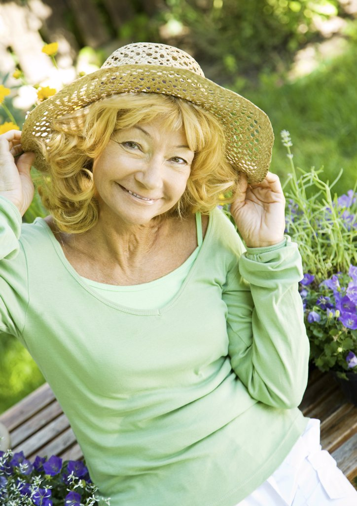 Senior woman wearing straw hat, portrait : Stock Photo