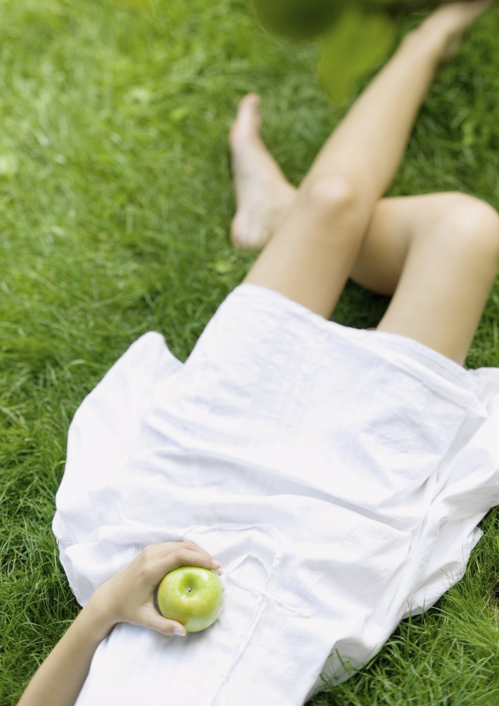 Stock Photo: 1747R-3519 Woman lying in grass, holding apple, low section