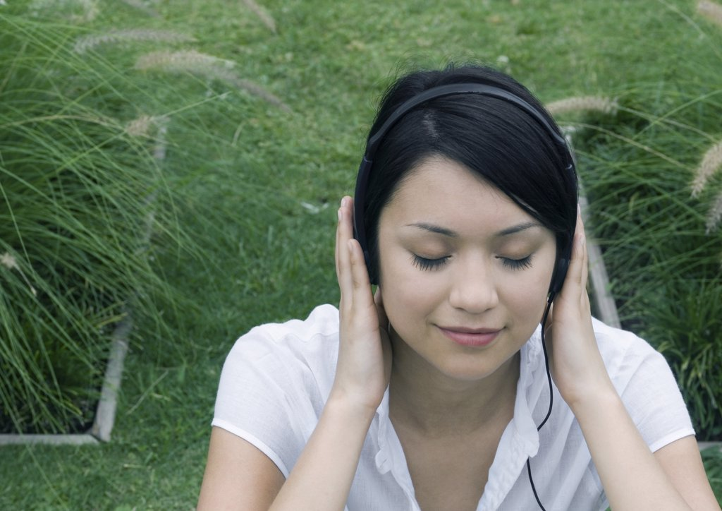 Woman sitting in ornamental garden, listening to headphones : Stock Photo