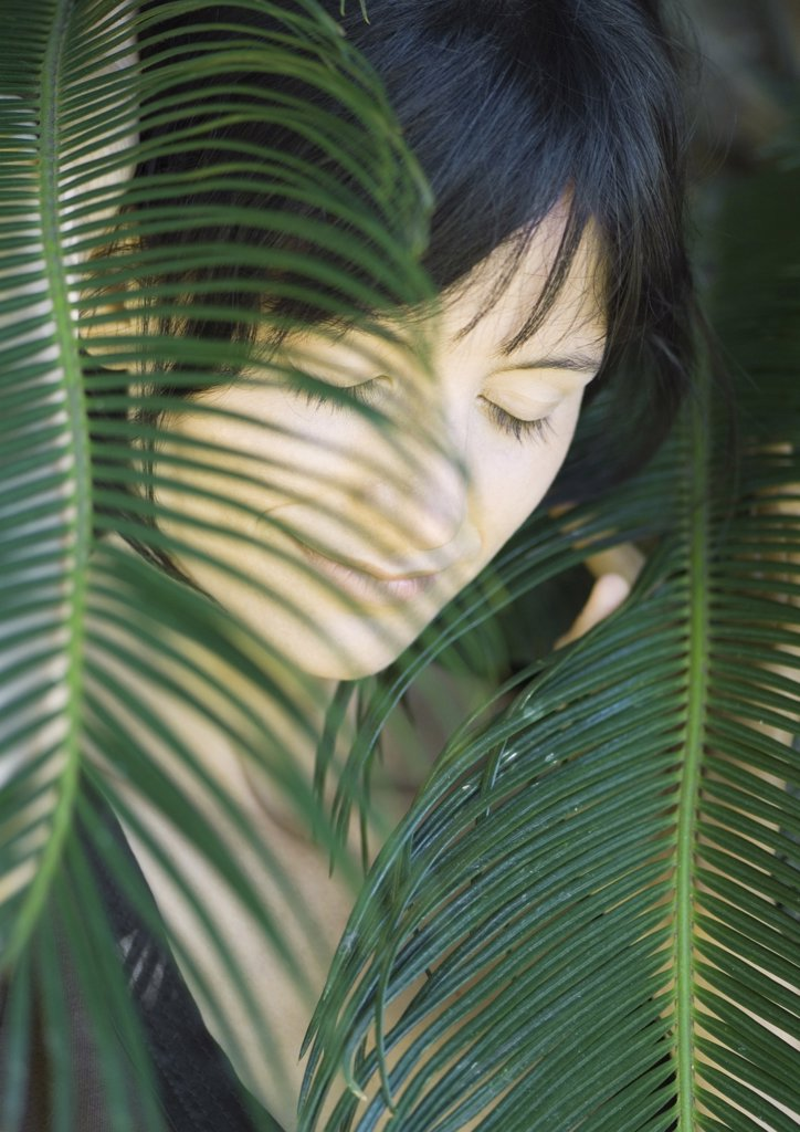 Stock Photo: 1747R-3843 Woman standing amongst leaves, head and shoulders