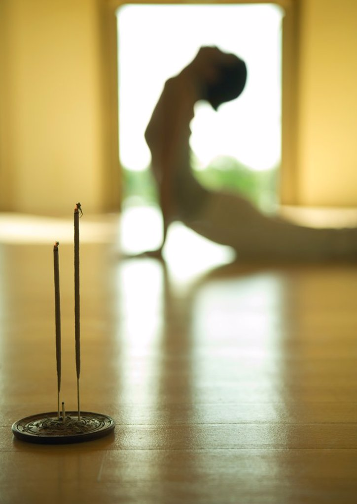 Stock Photo: 1747R-4281 Woman doing cobra pose, side view, focus on incense in foreground