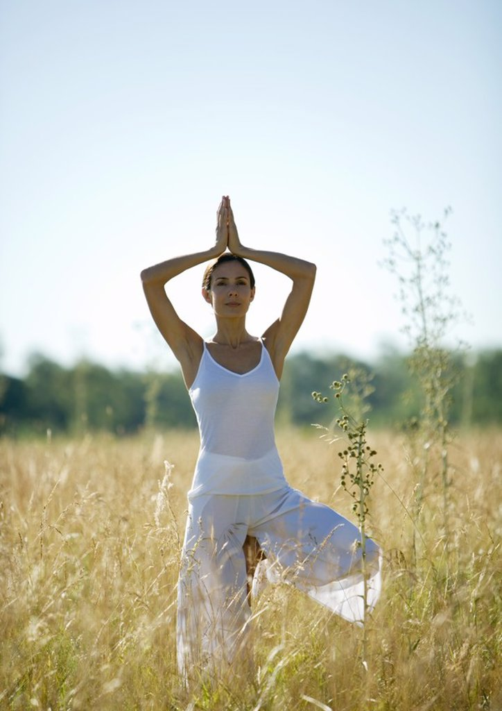 Woman doing yoga pose in field : Stock Photo