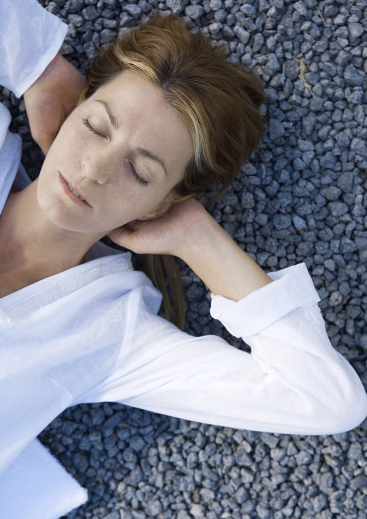 Stock Photo: 1747R-4459 Woman lying on gravel with hands behind head, eyes closed