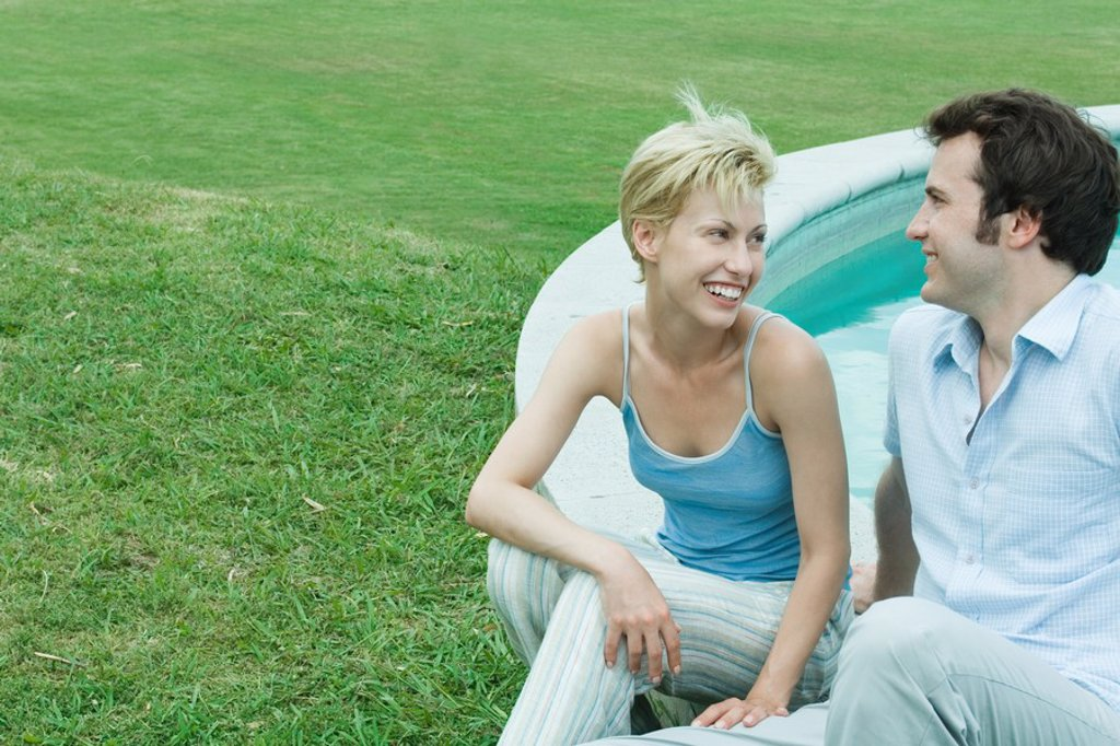 Stock Photo: 1747R-4724 Couple sitting by edge of pool, looking at each other, smiling
