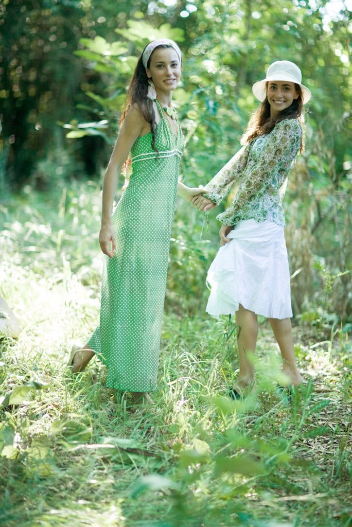 Two young women standing in woods, holding hands : Stock Photo