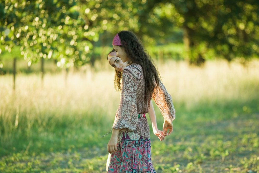 Stock Photo: 1747R-4881 Two young women walking outdoors, holding hands, one peeking at camera