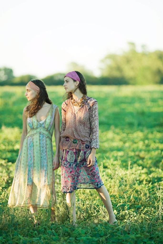 Stock Photo: 1747R-4883 Young hippie women standing in field, looking away, full length