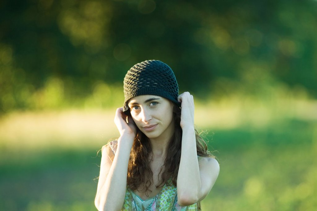 Young woman putting on hat : Stock Photo
