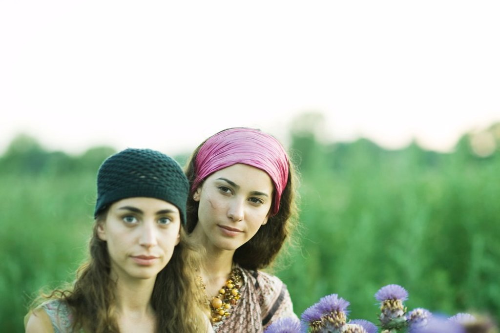 Young women standing in field, thistle in foreground : Stock Photo