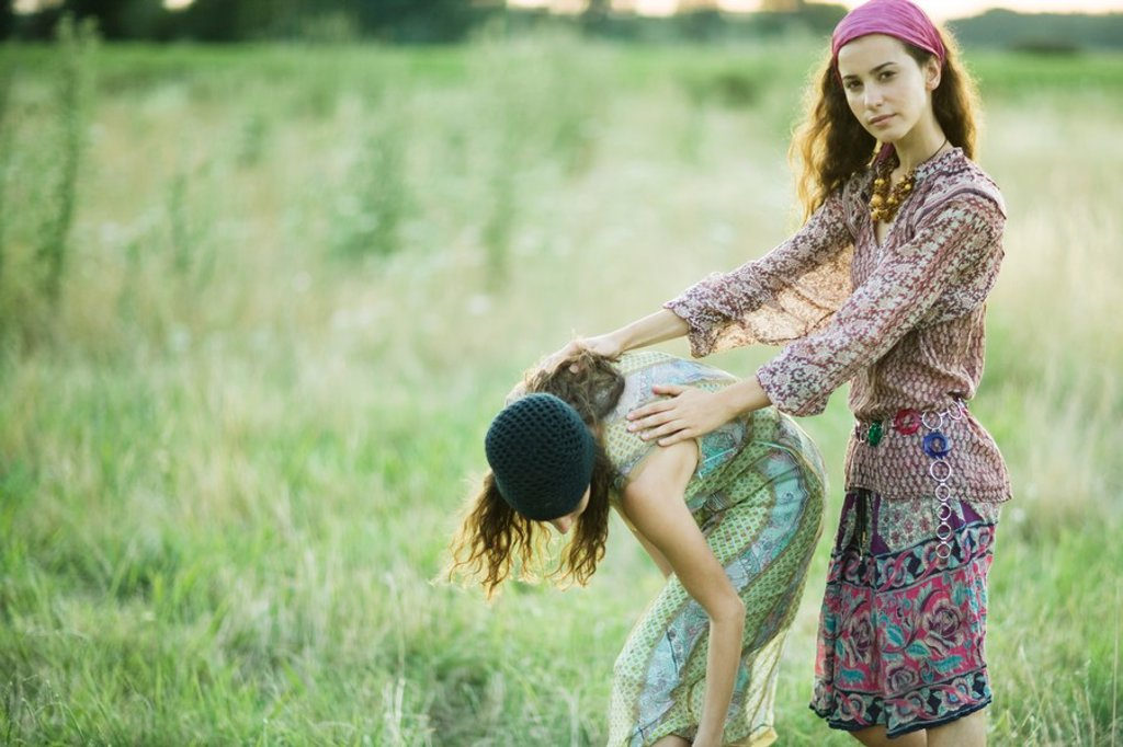 Young women in field, one bending over while the other holds her back : Stock Photo