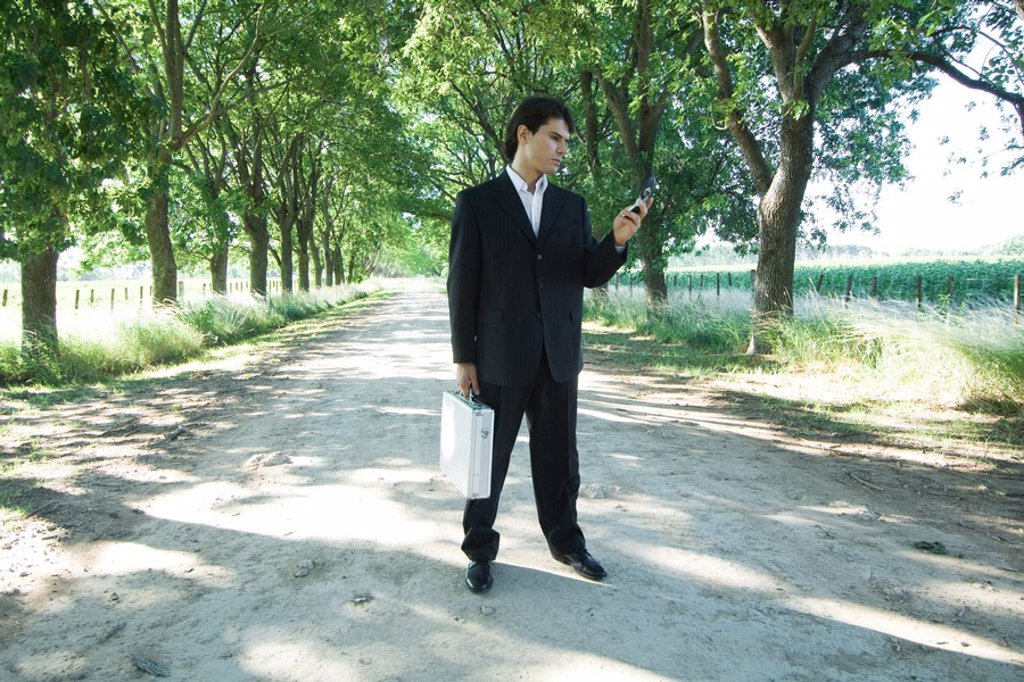 Stock Photo: 1747R-5152 Businessman standing in rural road, holding briefcase, looking at cell phone