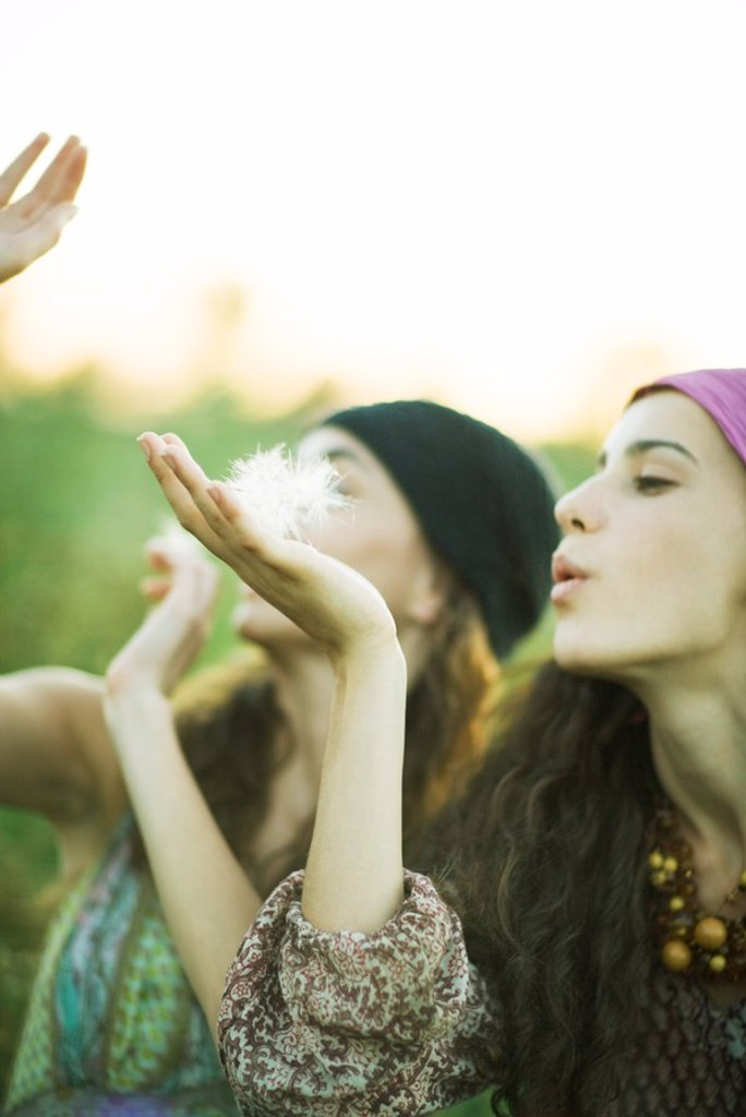 Stock Photo: 1747R-5755 Young hippie women blowing dandelion seeds