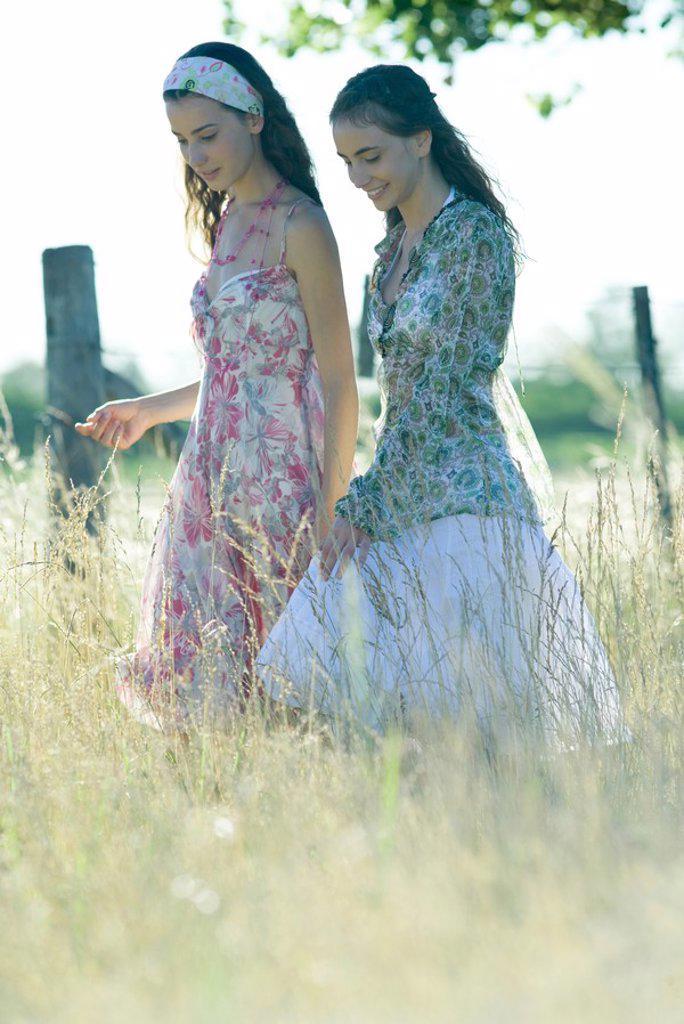 Young hippie women walking through field : Stock Photo