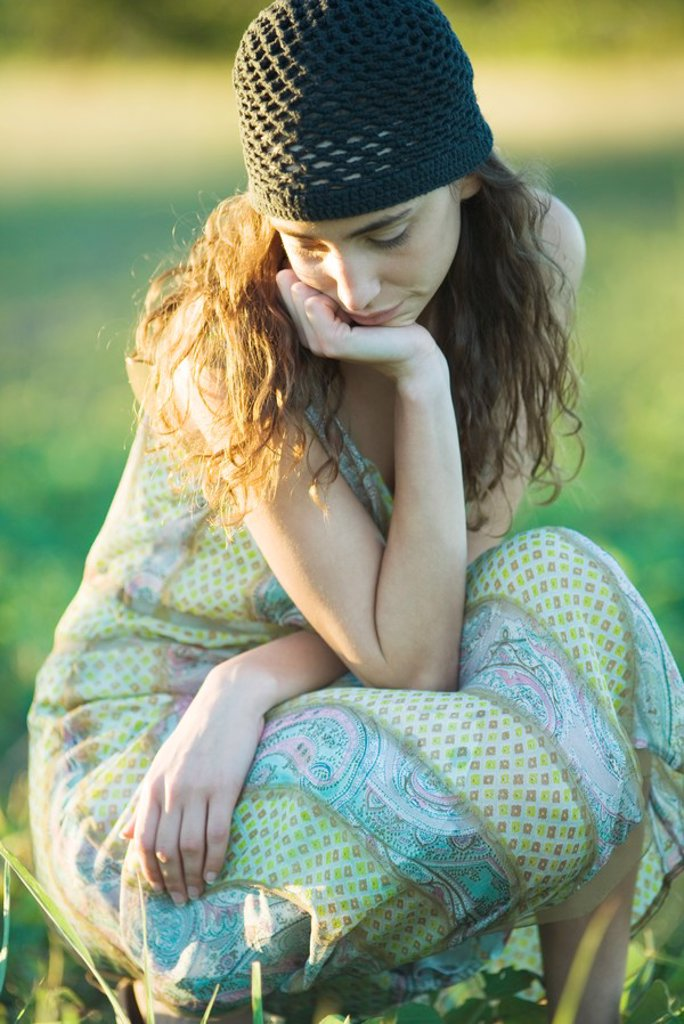 Young hippie woman crouching in grass, looking down : Stock Photo