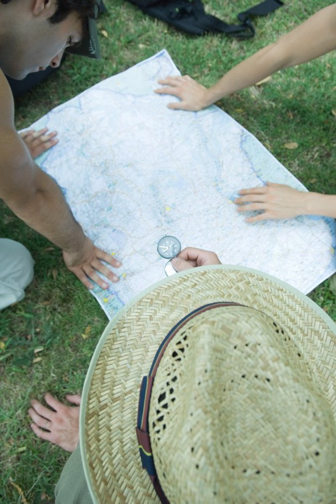 Hikers studying map, using compass : Stock Photo