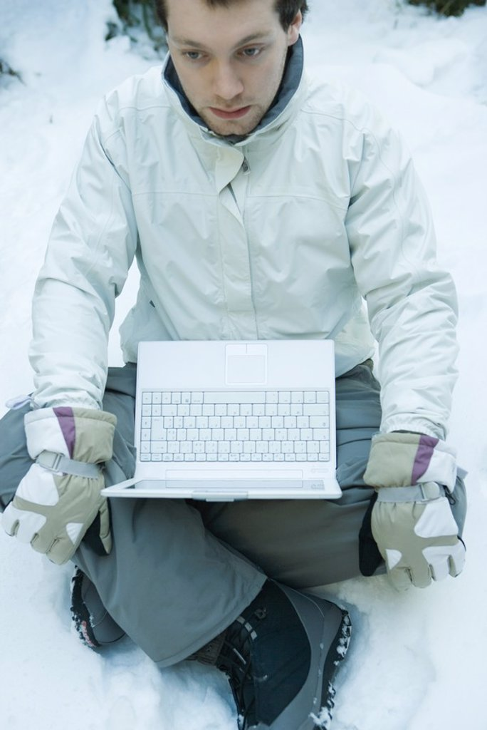 Young man sitting in snow, laptop on lap : Stock Photo
