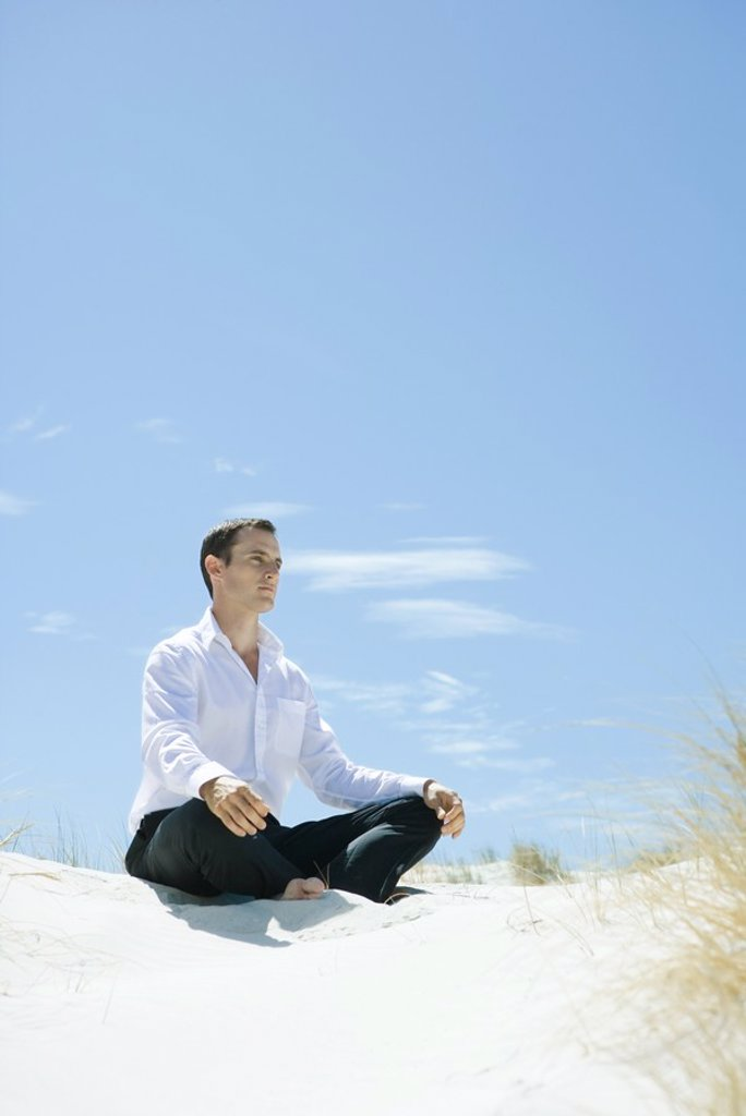 Stock Photo: 1747R-6197 Man sitting indian style on dune