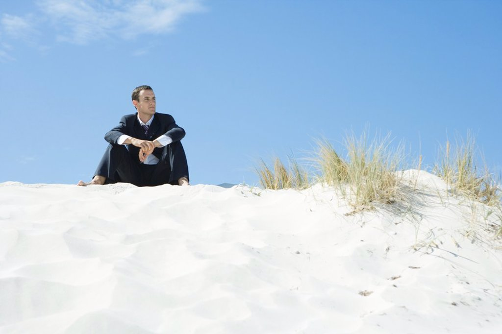 Businessman sitting on dune, looking at distance : Stock Photo