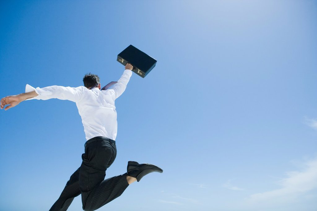 Stock Photo: 1747R-6228 Businessman jumping in air with briefcase held up high, sky in background, low angle view