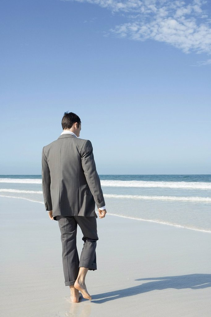 Stock Photo: 1747R-6413 Businessman walking barefoot on beach, rear view