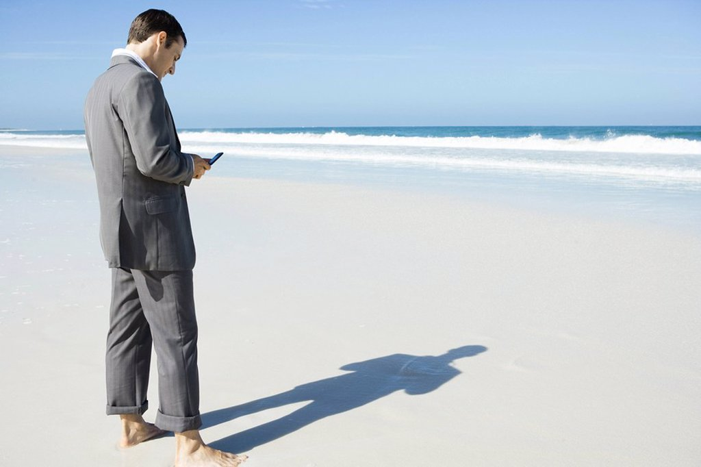 Stock Photo: 1747R-6419 Businessman standing barefoot on beach, looking at cell phone