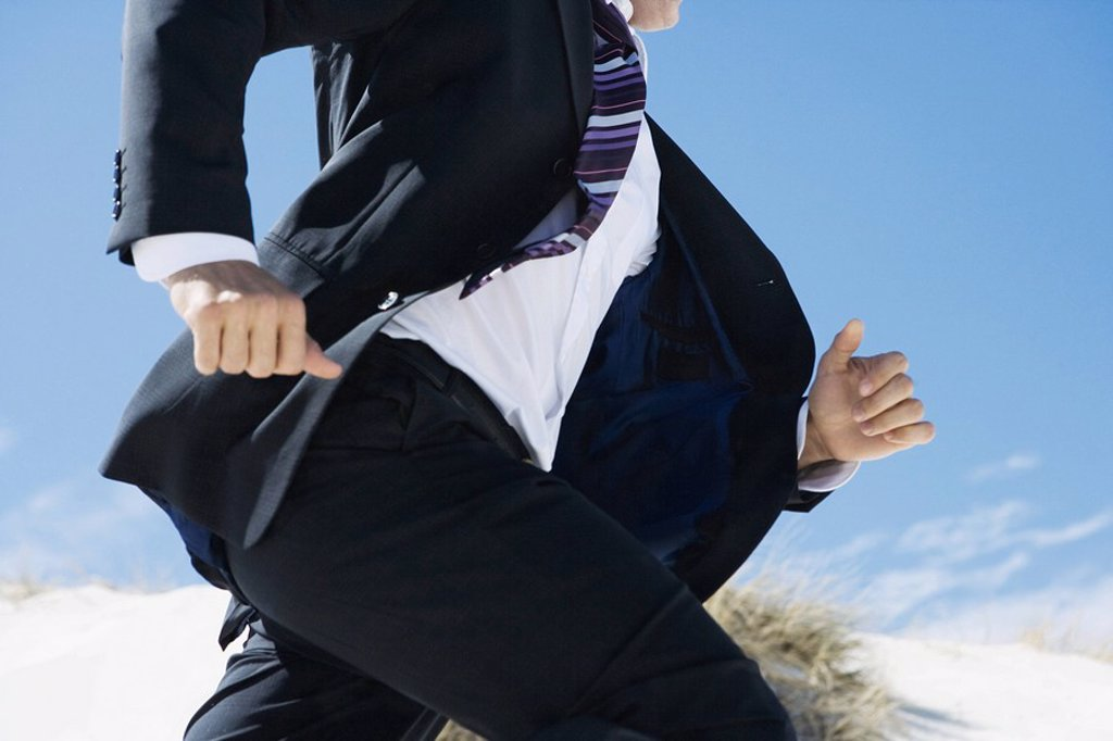 Stock Photo: 1747R-6431 Businessman running, sand dune in background, cropped view of mid section
