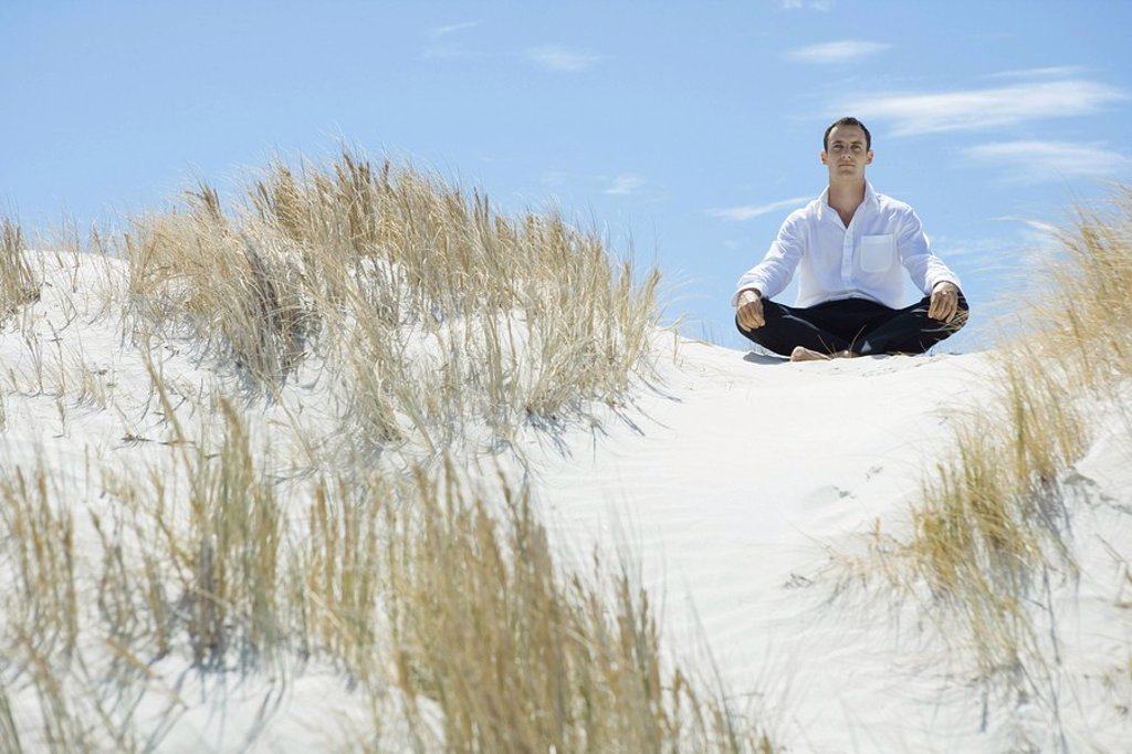 Businessman sitting on sand dune, indian style : Stock Photo