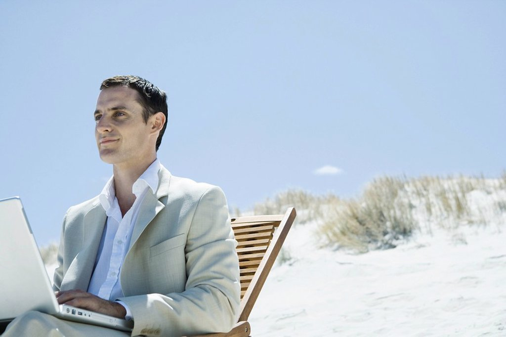 Businessman sitting in deck chair at beach, using laptop : Stock Photo
