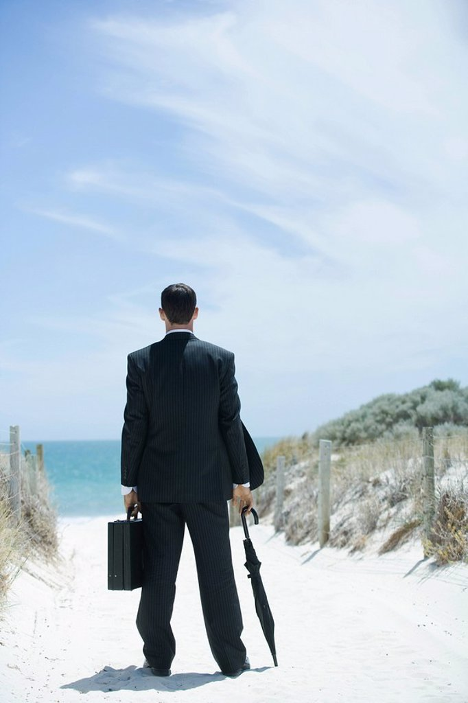 Businessman standing on sandy path leading to ocean, holding briefcase and umbrella, rear view : Stock Photo