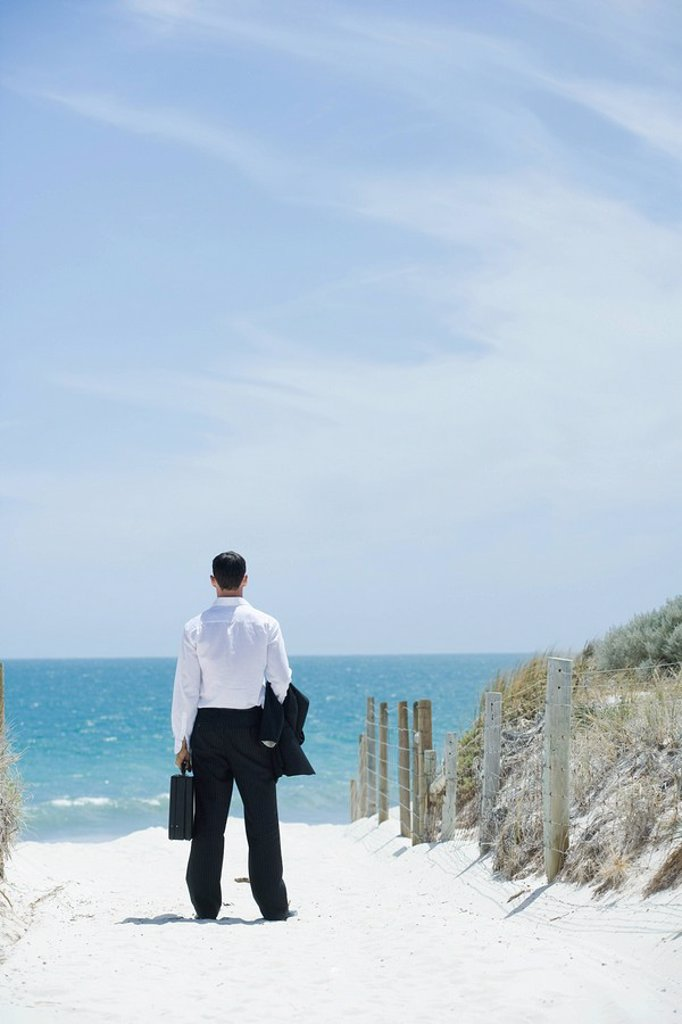 Businessman standing on sandy path leading to ocean, rear view : Stock Photo