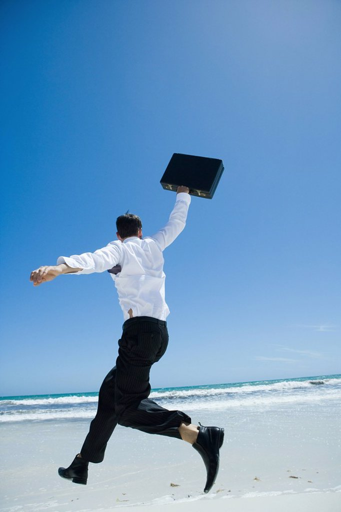 Businessman on beach, jumping into air with briefcase in hand : Stock Photo