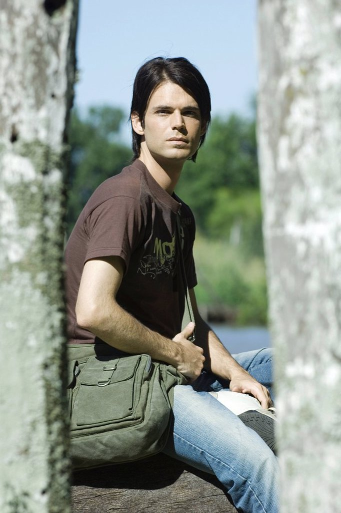 Man sitting outdoors wearing messenger bag : Stock Photo