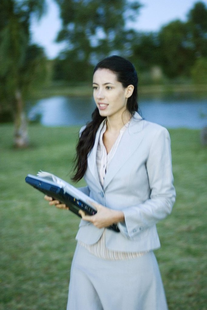 Businesswoman walking through park with laptop : Stock Photo
