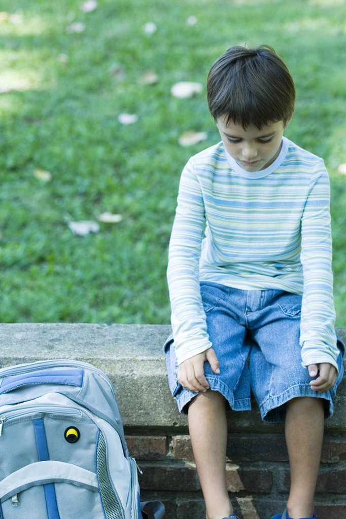 Boy sitting on low wall, backpack by side, looking down : Stock Photo