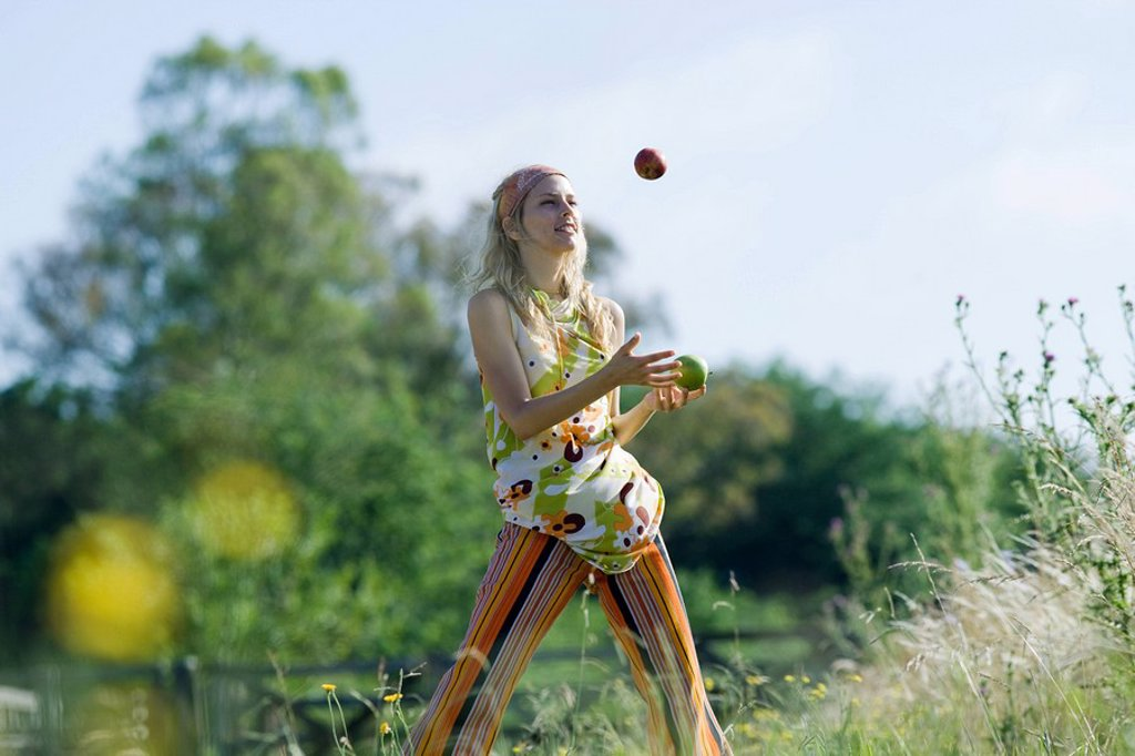 Young woman standing in field, juggling apples : Stock Photo