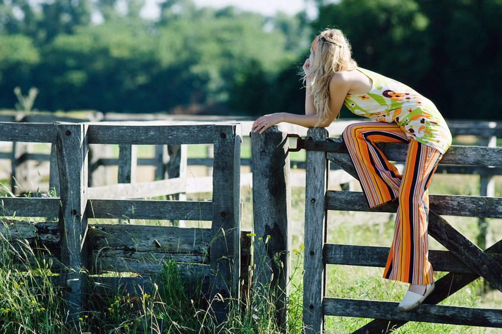 Young woman sitting on top of wooden fence, leaning on elbow, looking away : Stock Photo