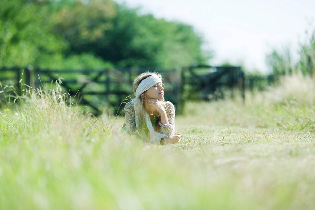 Young woman lying in field, eyes closed : Stock Photo
