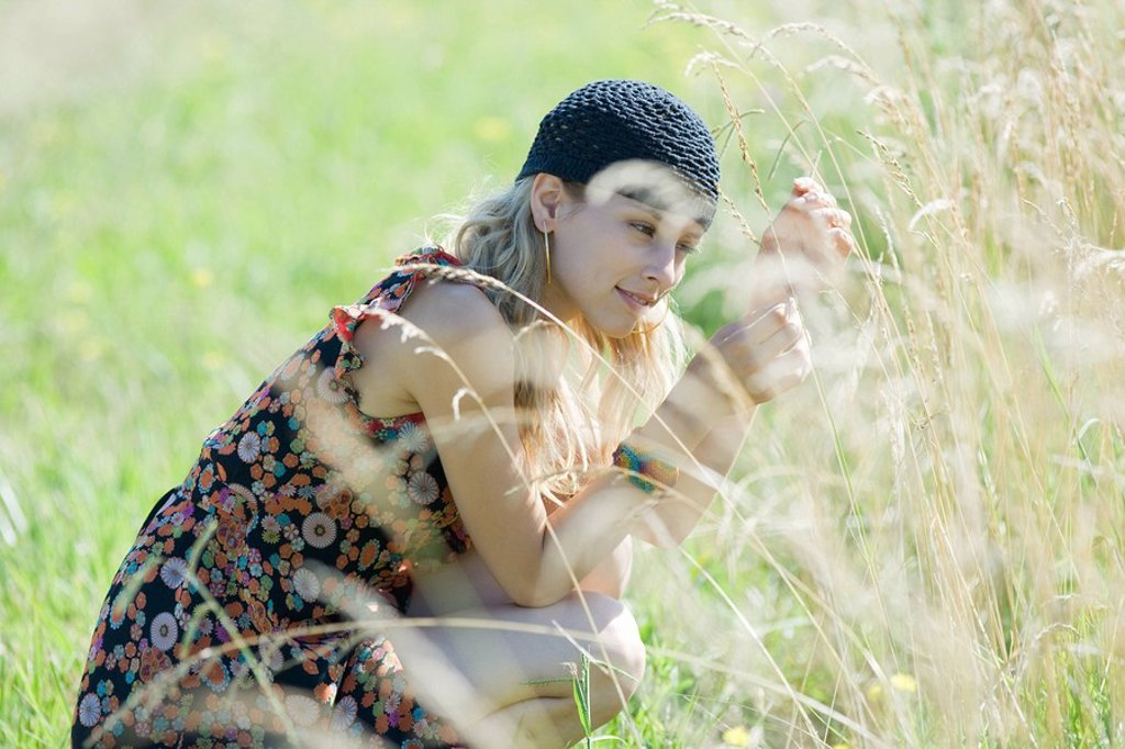 Stock Photo: 1747R-6764 Young woman crouching in field, touching tall grass