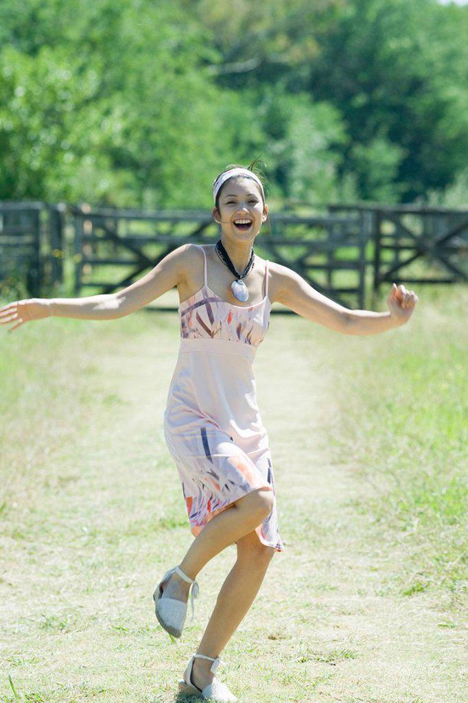 Stock Photo: 1747R-6819 Young woman running along rural path, smiling at camera