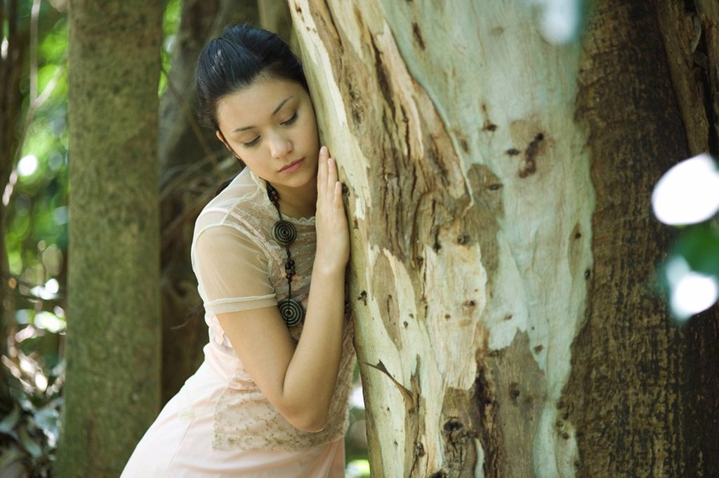 Stock Photo: 1747R-6834 Young woman leaning head against tree trunk, eyes closed