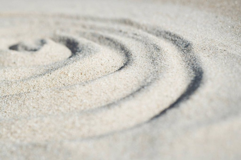 Spiral shape drawn in sand, close-up, surface level : Stock Photo