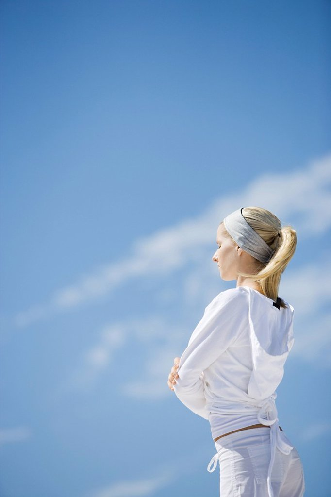 Young woman standing with eyes closed and arms crossed, side view, sky in background : Stock Photo